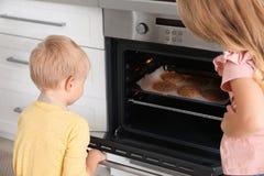 Kleine jonge geitjes die koekjes in oven bakken stock afbeeldingen
