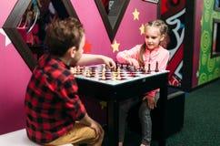 Kleine jonge geitjes die schaak in vermaakcentrum spelen stock afbeelding