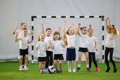 Kleine jonge geitjes die voetbal binnen spelen Het Team van de kinderenvoetbal Handen omhoog en springend royalty-vrije stock foto