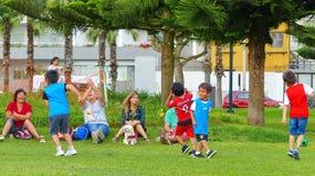 Kleine jonge geitjes die voetbal spelen bij Miraflores-park stock foto's