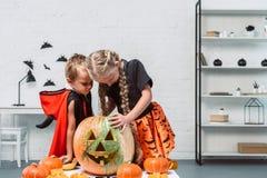 kleine jonge geitjes in Halloween-kostuums die pompoen onderzoeken royalty-vrije stock afbeeldingen
