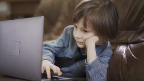 Kleine jongen die aan een laptop computer op de leerbank werken stock videobeelden