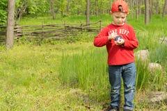 Kleine jongen die een gelijke aansteken om een kampvuur te beginnen Stock Afbeeldingen