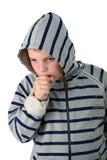 Kleine jongen die in een kap hoest die op wit wordt geïsoleerdk Royalty-vrije Stock Foto's