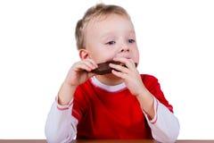 Kleine jongen die gehele reep chocolade eten Stock Afbeeldingen