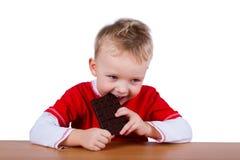 Kleine jongen die gehele reep chocolade eten Stock Fotografie