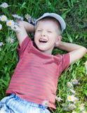 Kleine jongen die op het gras ligt stock afbeeldingen