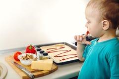 Kleine jongen die pizza maken Stock Afbeeldingen