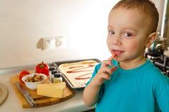Kleine jongen die pizza maken Stock Afbeelding