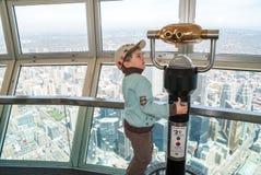 Kleine jongen die telescoop op CN toren gebruiken Royalty-vrije Stock Foto