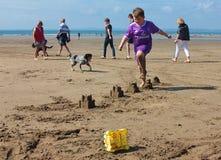Kleine jongen het springen zandkastelen op het strand Augustus 2018 stock foto