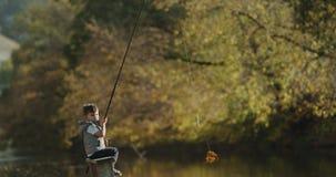 Kleine jongen met het charismatische gezicht spelen met een staaf tot het zijn onderwijs hoe te om de vissen te vangen stock footage