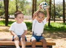 Kleine jongens: Afrikaanse Amerikaans en Kaukasisch met voetbalbal in park op aard bij de zomer Stock Foto
