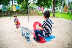 Kleine jongens die geschommel samen in het park spelen royalty-vrije stock foto's