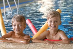 Kleine jongens met zwemmende noedels in pool stock fotografie
