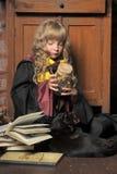 Kleine junge Hexe mit schwarzer Katze und Büchern Stockbilder
