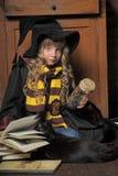 Kleine junge Hexe mit schwarzer Katze und Büchern Lizenzfreies Stockbild