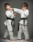Kleine Jungen in übendem Judo der Uniform Lizenzfreie Stockbilder