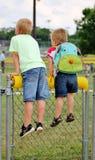 Kleine Jungen auf einem Zaun, der auf ein Baseballfeld schaut Lizenzfreie Stockbilder
