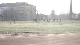 Kleine Jungen, die Fußball auf dem Sportfeld nahe bei Ziel spielen Junge spielt Fußball am Sonnenscheintag stock video