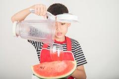 Kleine Jungen mischen Wasser melone Saft, indem sie Mischmaschinenhaus verwenden lizenzfreies stockfoto