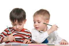 Kleine Jungen schreiben am Schreibtisch Stockbilder