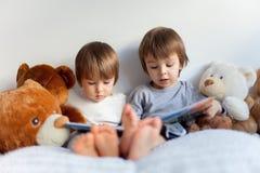 Kleine Jungen, sitzend im Bett und lesen ein Buch Stockbilder
