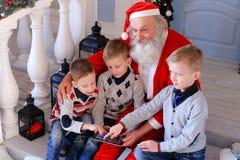 Kleine Jungen stellten neue Tablette durch Vater Christmas vor Stockfotos