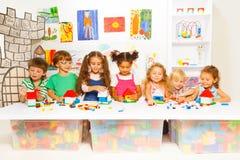 Kleine Jungen und Mädchen, die Spielzeughäuser konstruieren Stockfotografie