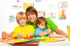 Kleine Jungen und Vaterhandwerk mit Kleber Stockfoto