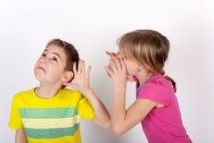 Kleine Jungenneigung hören Stockfotos