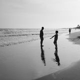 Kleine Jungenspiele durch den Ozean Lizenzfreies Stockfoto