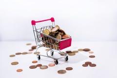 Kleine kar met muntstukken op witte achtergrond Stock Foto