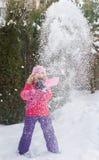 Kleine kaukasische blonde Mädchen in der roten Jacke spielt mit Schnee auf Tannenbaumunschärfehintergrund Lizenzfreies Stockfoto