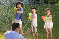 Kleine kerels die waterkanonnen gebruiken om hun vader te bespuiten royalty-vrije stock afbeelding