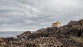 Kleine kerk van Santa Catalina op de kust van Mundaca-dorp in Biskaje tijdens een bewolkte dag royalty-vrije stock afbeelding