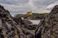 Kleine kerk van Santa Catalina op de kust van Mundaca-dorp in Biskaje tijdens een bewolkte dag stock foto's