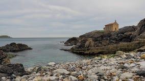 Kleine kerk van Santa Catalina op de kust van Mundaca-dorp in Biskaje tijdens een bewolkte dag stock afbeelding