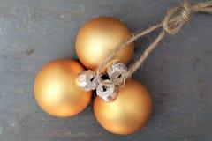 Kleine Kerstmisballen op een kabel met steenachtergrond Stock Foto
