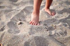 Kleine Kind-` s Füße auf dem sandigen Strand im Sommer stockfotos