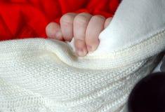 Kleine kind` s hand op een witte wollen sjaal sjaal stock foto