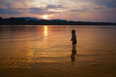 Kleine kind thwrowing stenen aan de rivier ath zonsondergang royalty-vrije stock foto
