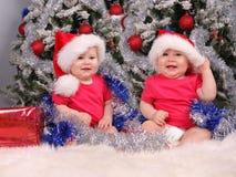 Kleine Kinder in den Schutzkappen über Weihnachtsbaum stockfotos