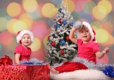 Kleine Kinder in den Schutzkappen über Weihnachtsbaum stockbilder