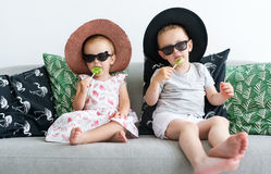 Kleine Kinder in den schwarzen Gläsern, die zu Hause mit Lutschern auf Trainer im Wohnzimmer mit Hüten sitzen Stockbilder