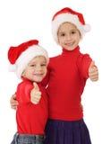 Kleine Kinder in den Weihnachtshüten und im okayzeichen Lizenzfreies Stockbild