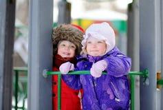Kleine Kinder in der Winterkleidung, die Spaß auf Spielplatz am Tag des verschneiten Winters hat Stockfoto