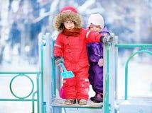 Kleine Kinder in der Winterkleidung, die Spaß auf Spielplatz am Tag des verschneiten Winters hat Stockfotos