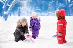 Kleine Kinder in der Winterkleidung, die Spaß im Park am Tag des verschneiten Winters hat Lizenzfreies Stockfoto