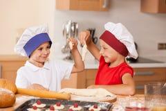 Kleine Kinder, die Bäckerei und das Lächeln machen Stockfotografie
